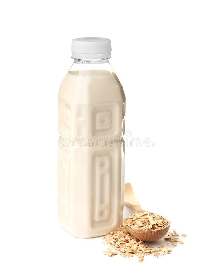 Bottle with oat milk and flakes. On white background royalty free stock photography