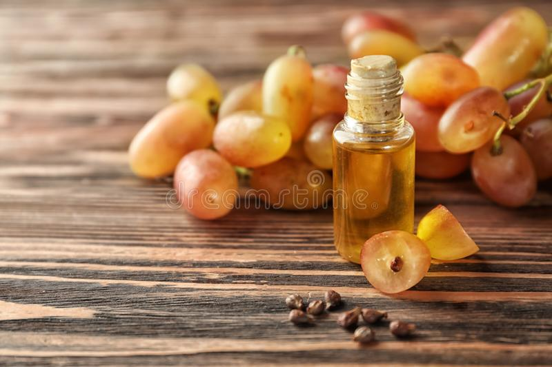 Bottle with oil and fresh ripe grapes on wooden background stock photography