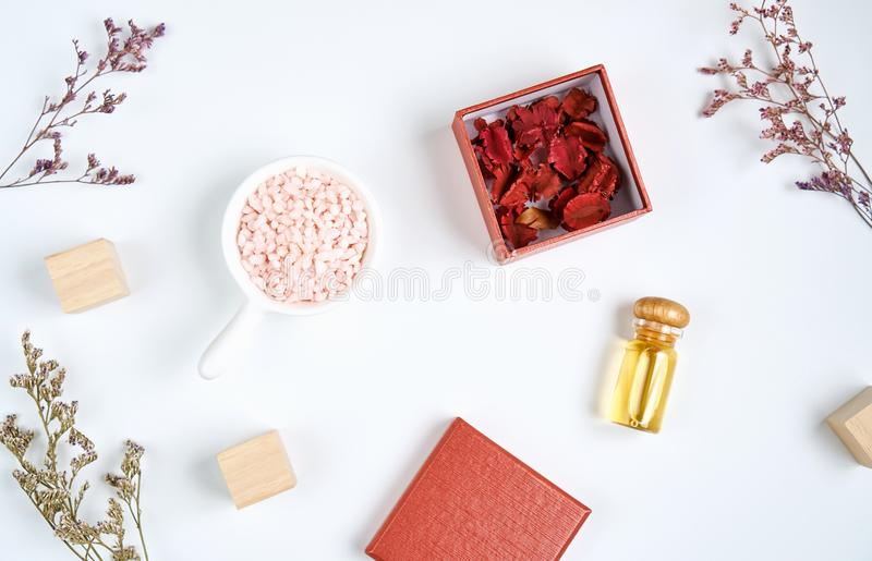 Bottle of oil placed, Contains natural extracts in the ingredients and a beautiful red fill. Blank label package for mock up on white background and flowers stock image