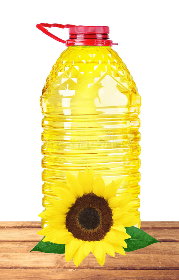 Bottle oil plastic big and sunflower on table on white. Background stock photos