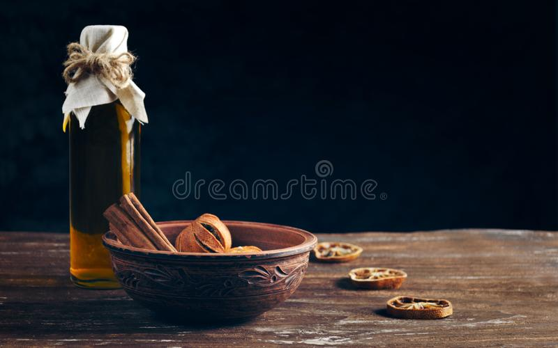 Bottle with oil and a plate with dried fruits on a wooden table royalty free stock photo