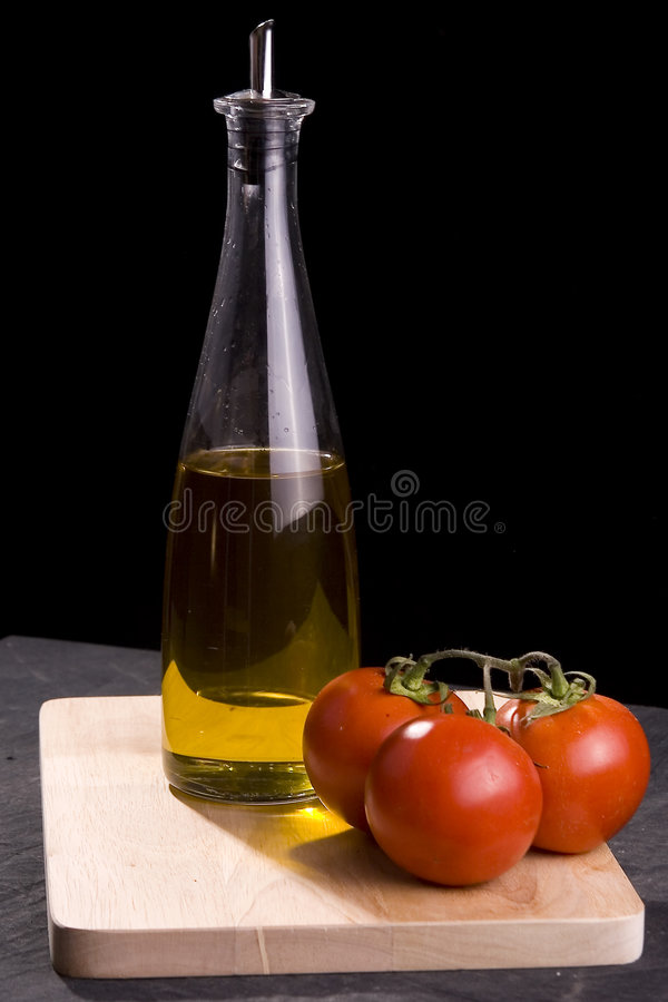 Bottle of oil and red tomatoes stock image