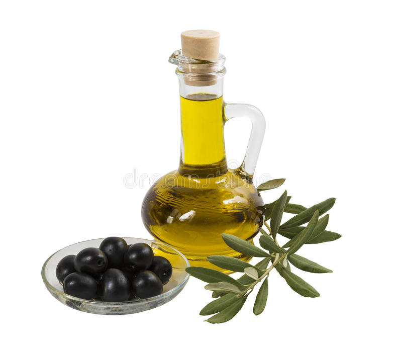 A bottle with olive oil, black olives on a plate and olive branch with leaves on a white background stock image