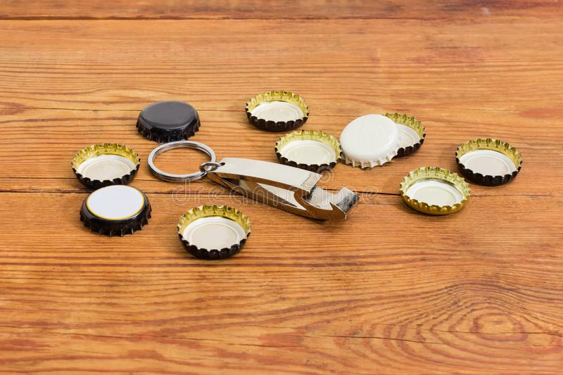 Bottle opener in form of keychain among of bottle caps stock images