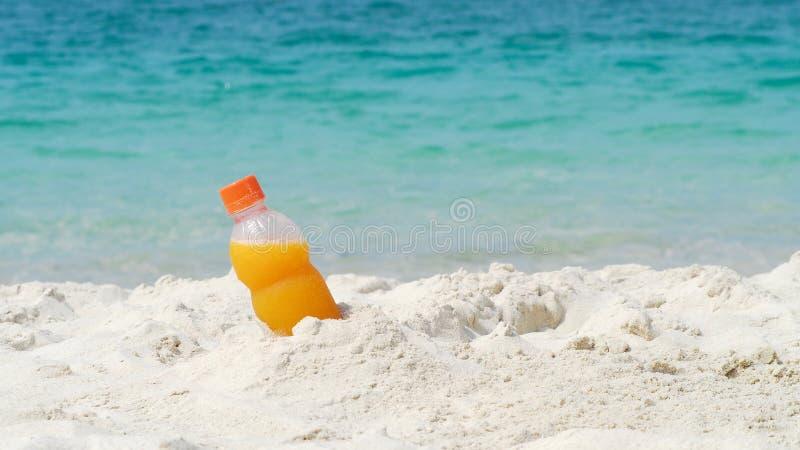 Bottle of orange juice on the beach. In summer stock photo