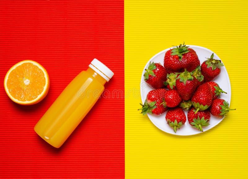 Bottle orange juice strawberry on orange yellow background royalty free stock photography