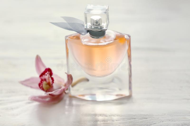 Bottle of perfume with tropical flower on white wooden table stock images
