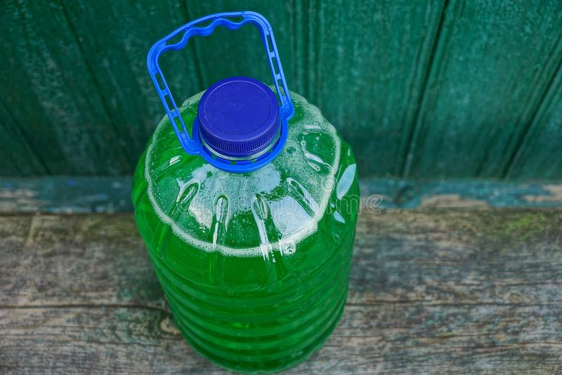 Large plastic bottle with green liquid on a wooden board. A bottle of plastic with a green liquid on a bench near the wall royalty free stock images