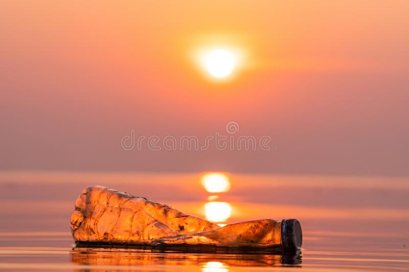 Bottle plastic in the lake. Outdoor on the baking hot day with sunrise morning, Drought and environmental problems and pollution concept royalty free stock image
