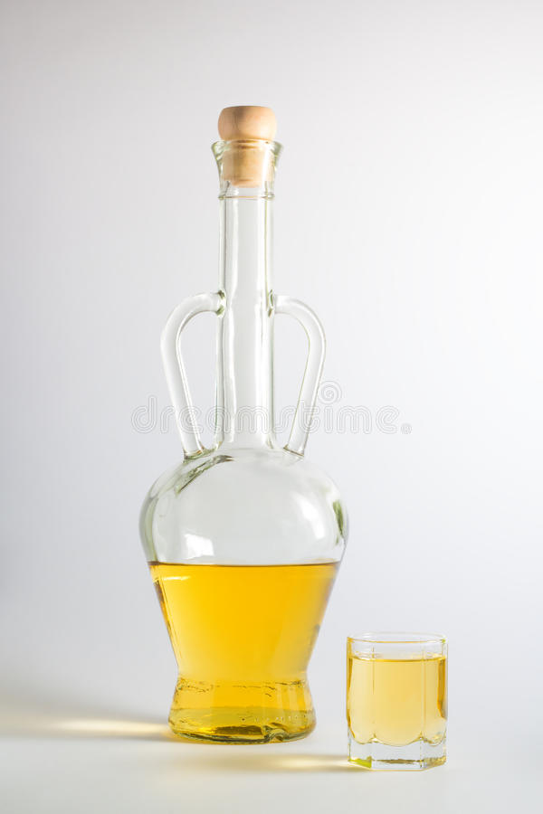 Bottle of Plum Brandy with a glass. Bottle of plum brandy, slivovitz, with a brandy glass, on white background stock photos