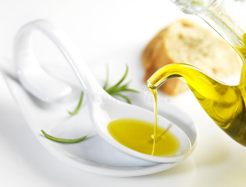 Virgin olive oil pouring in a spoon royalty free stock image