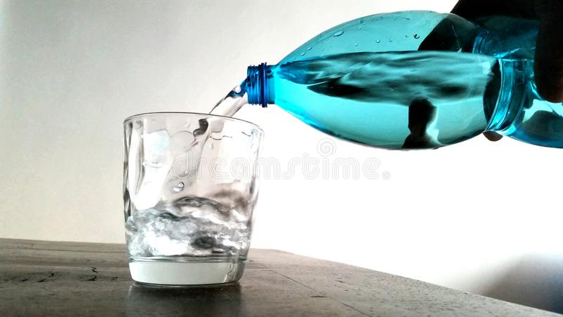 Bottle pouring water. Blue bottle pouring water on white background stock image