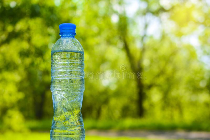 A bottle of pure clear water with drops on the surface against the backdrop of greenery and copy space.  stock photos
