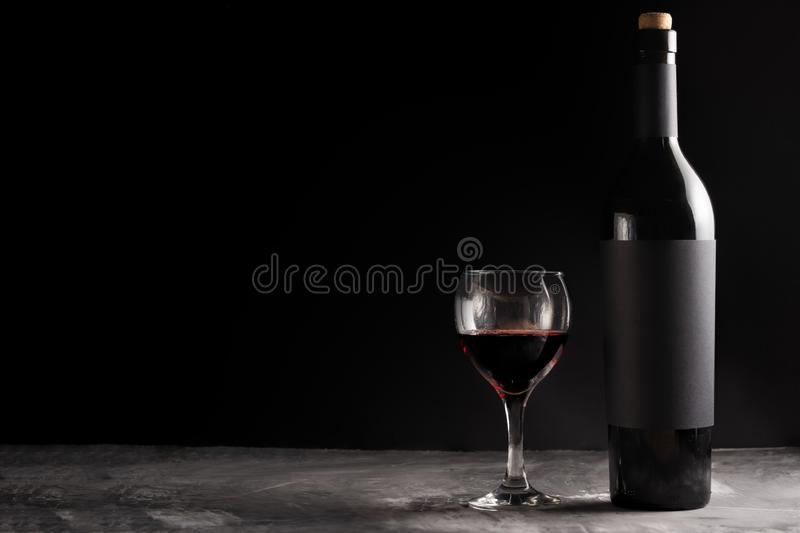 A bottle of red expensive wine with a black blank label on a dark background with a glass of red wine. Wine bottle mockup with. Space for text royalty free stock images