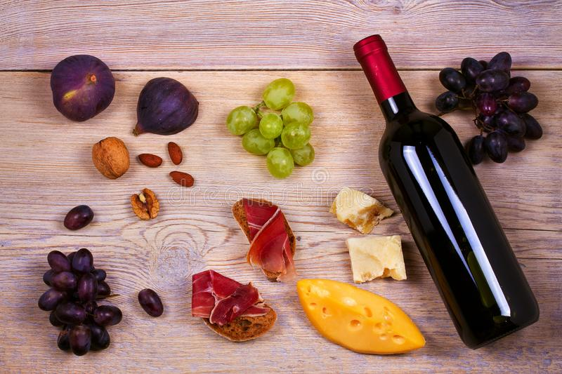 Bottle of red and white wine with cheese, prosciutto, figs and grape. Wine still life. Food and drinks concept. royalty free stock photography