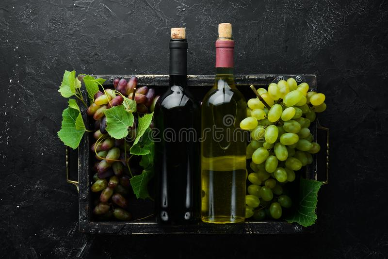 Bottle of red and white wine and grapes on a black stone table. Top view. Free space for your text stock image