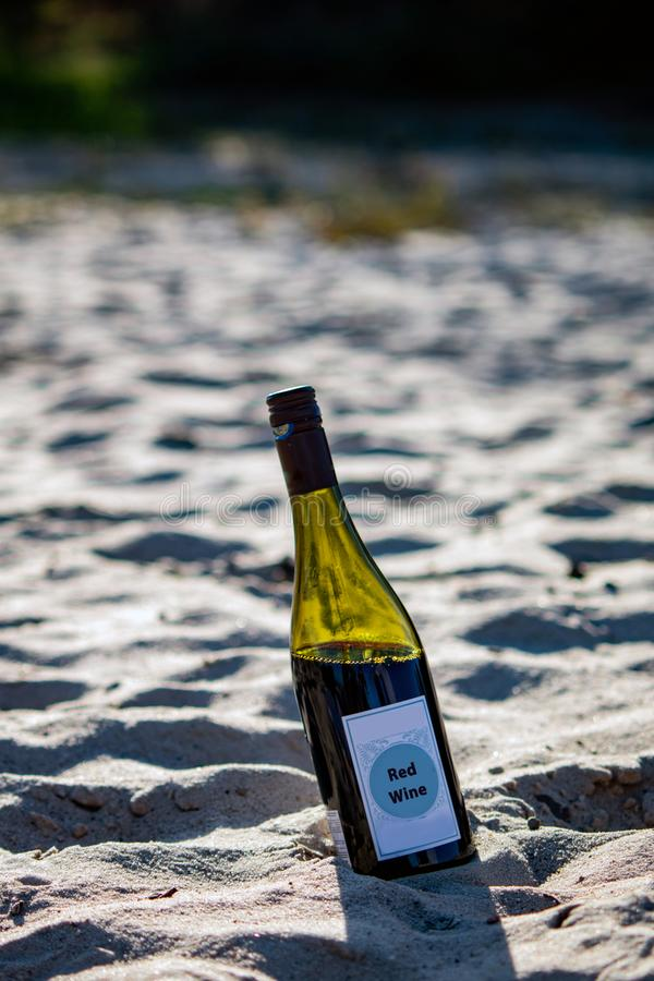 Bottle of red wine on the beach stock photos