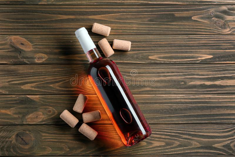 Bottle of red wine with corks on wooden background stock images