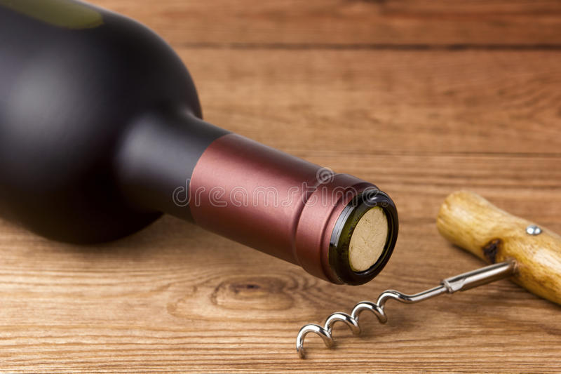 Bottle of Red Wine and Corkscrew stock images