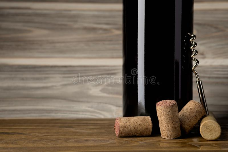 Bottle of red wine with a corkscrew and corks. On a wooden table royalty free stock image