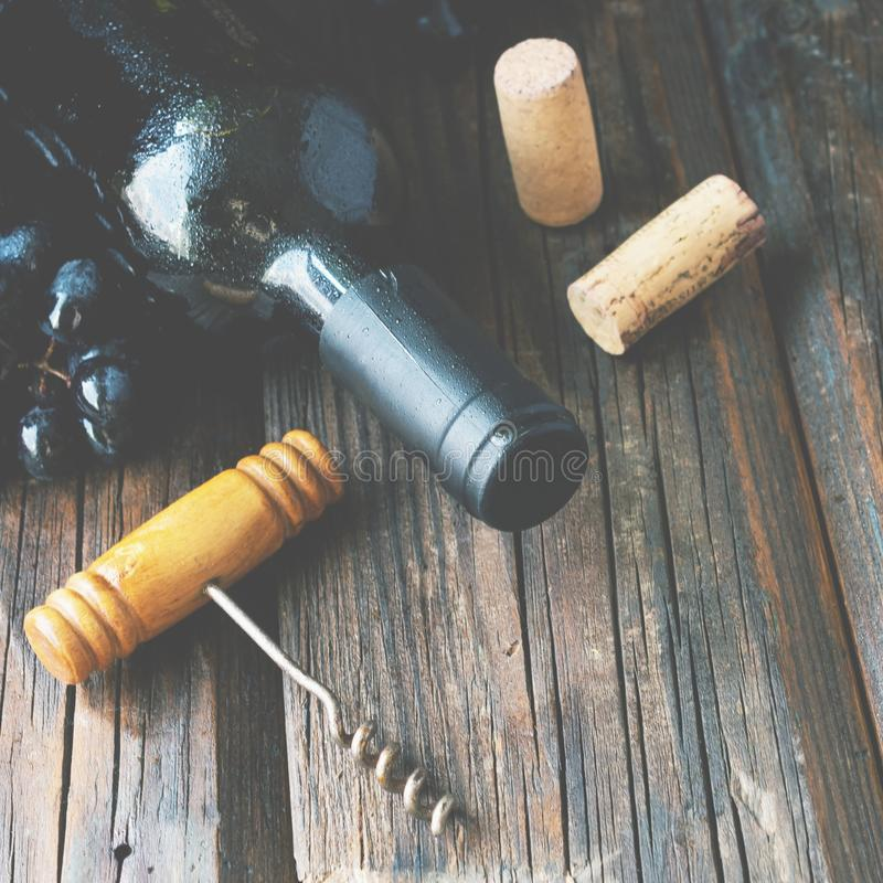 Bottle of red wine with fresh grape and bunch of corks on wooden table stock photos