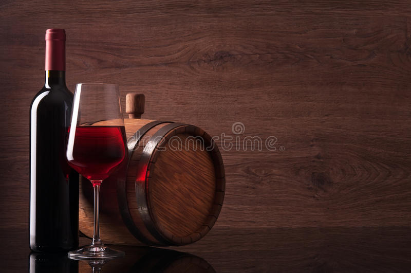 Bottle of red wine, glass and barrel on wooden background stock images