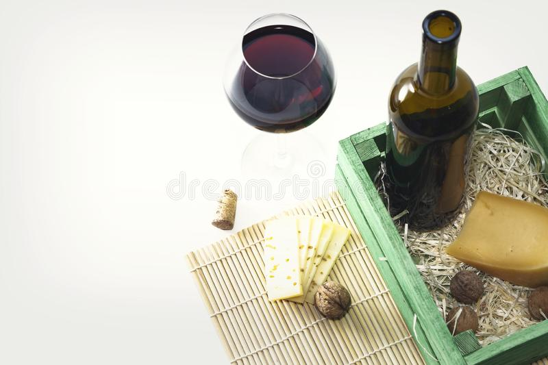 A bottle of red wine with a glass and a piece of cheese.  stock photography