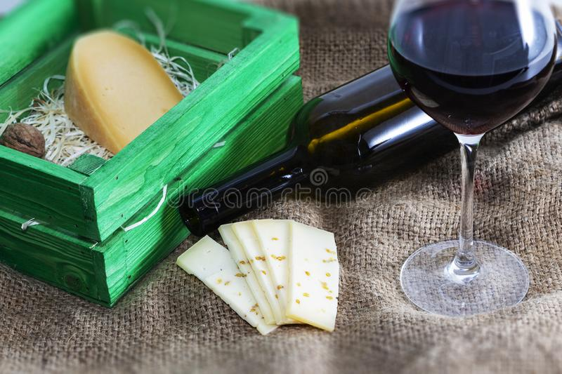 A bottle of red wine with a glass and a piece of cheese. A bottle of red wine with a glass and a piece of cheese royalty free stock images