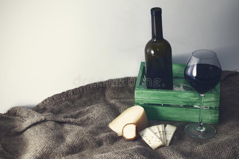 A bottle of red wine with a glass and a piece of cheese.  royalty free stock image