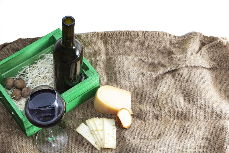 A bottle of red wine with a glass and a piece of cheese.  stock images