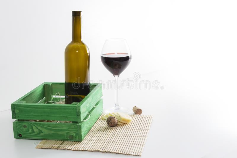 A bottle of red wine with a glass and a piece of cheese.  stock image