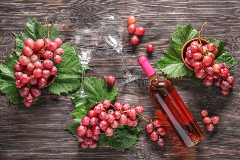 Bottle of red wine, glasses and ripe grapes on wooden table stock photo