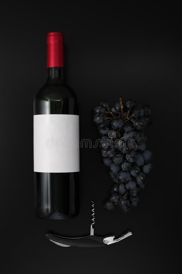 Bottle of red wine with label, corkscrew  and ripe grapes stock photography