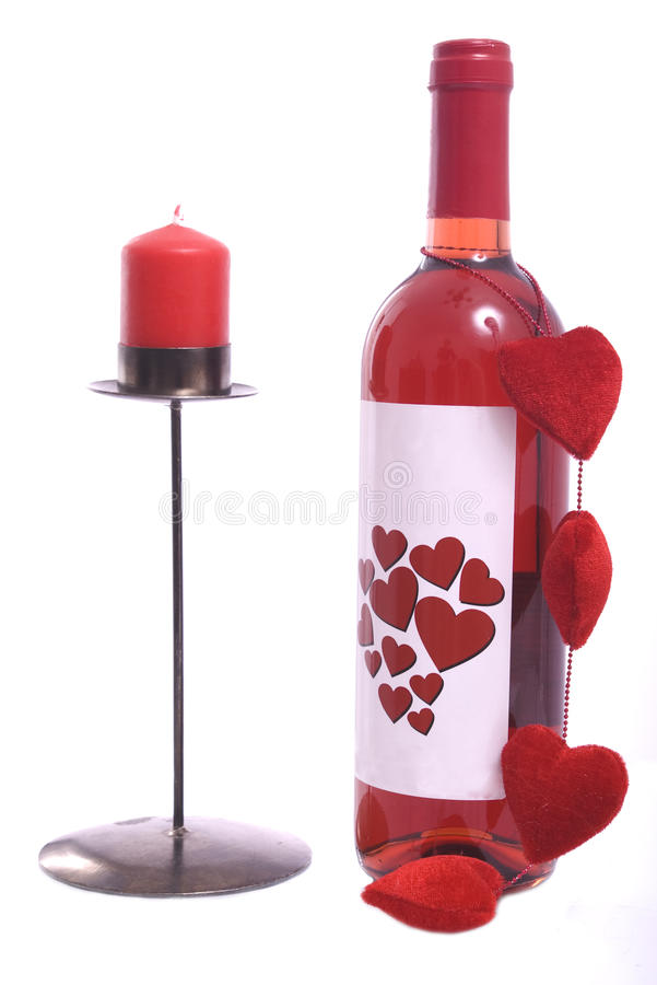 Bottle of red wine with red candle stock photography