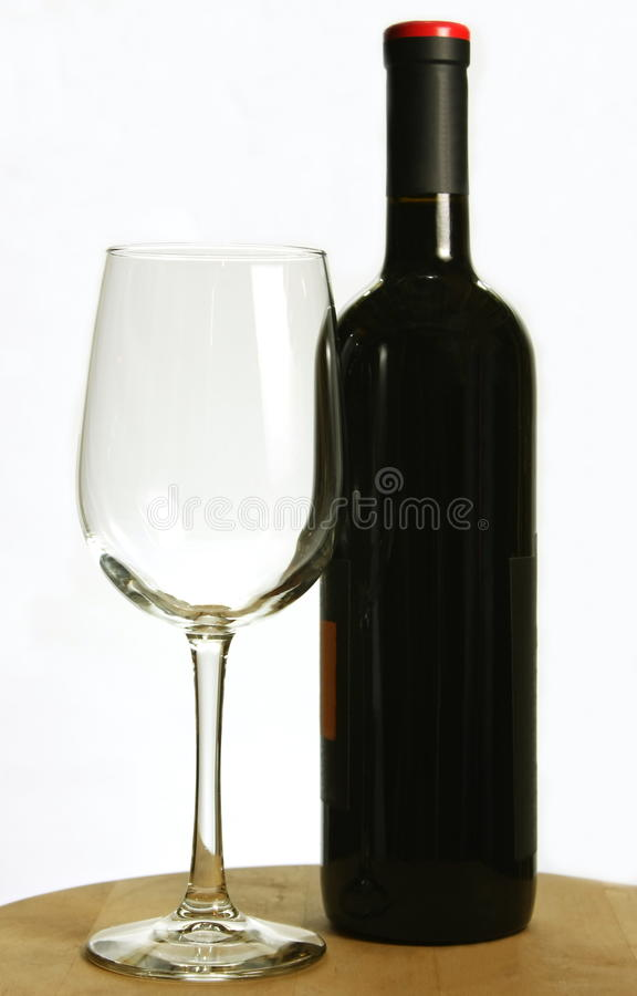 Bottle of red wine and single wine glass
