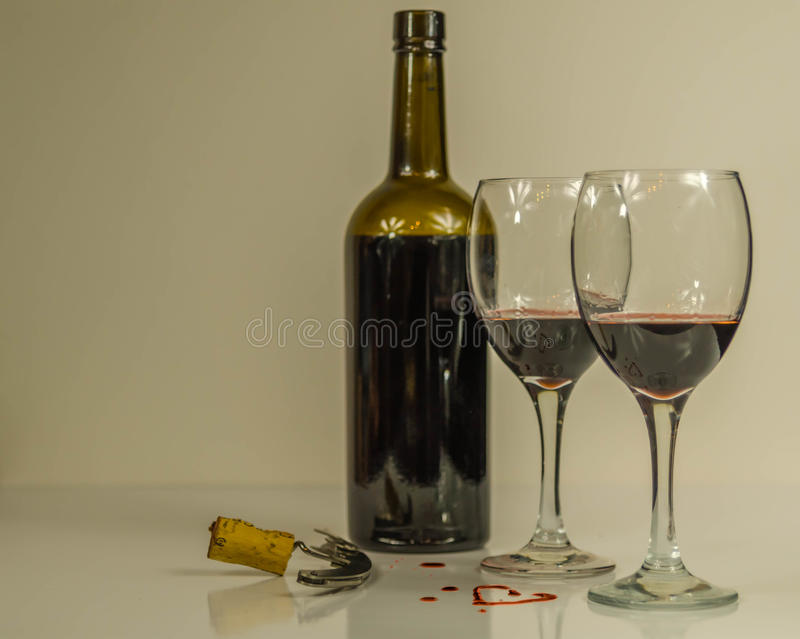 Bottle of red wine with two glasses and heart. Corkscrew with cork stock images