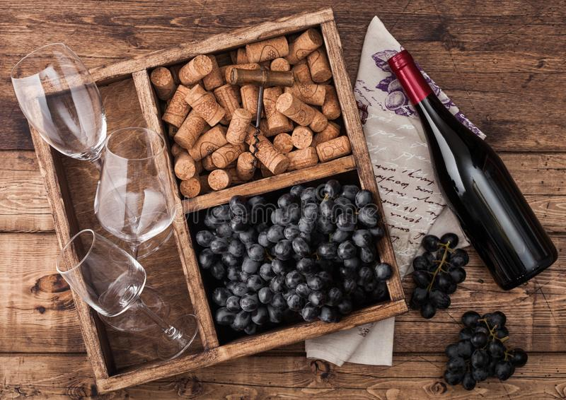 Bottle of red wine on wood with empty glasses with dark grapes with corks and opener inside vintage wooden box on grunge wooden stock image