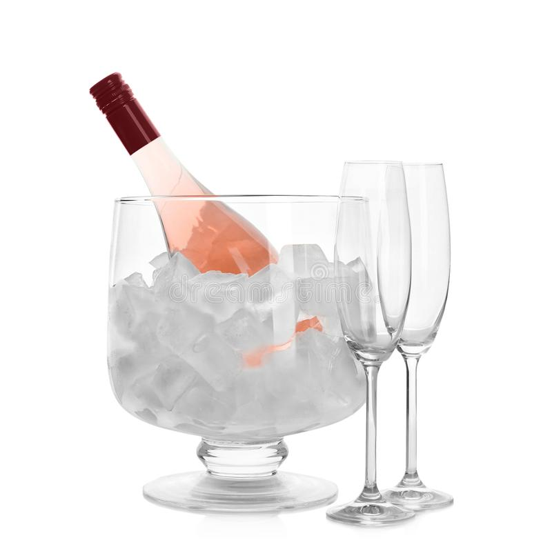 Bottle of rose champagne in vase with ice and flutes stock photo