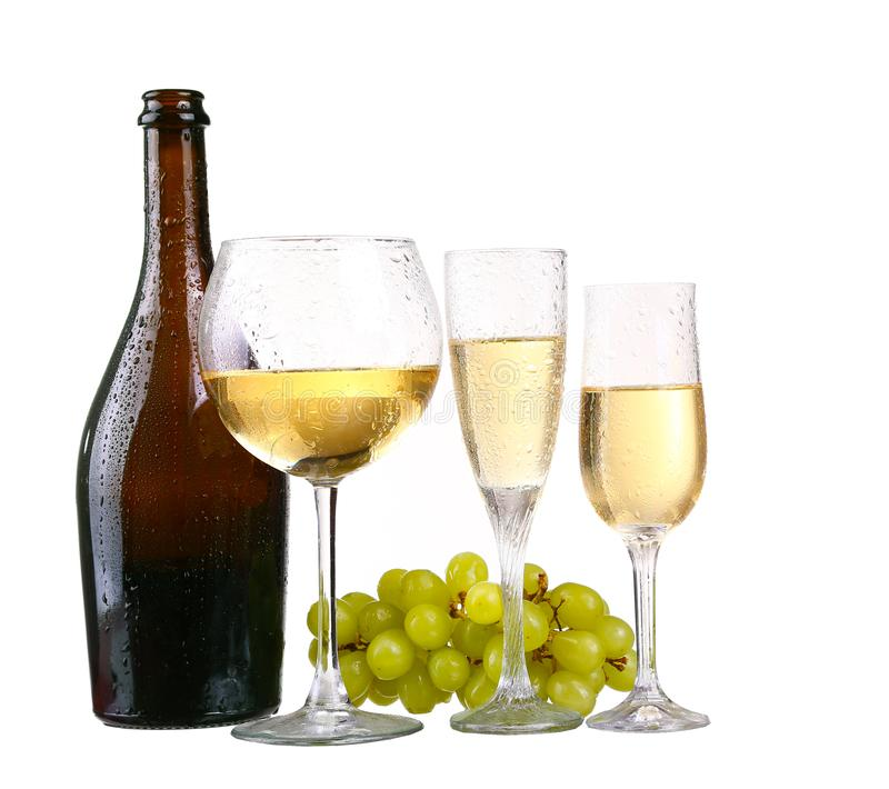 Bottle, a row of white wine glasses with wine and grapes isolated. On white background royalty free stock photos