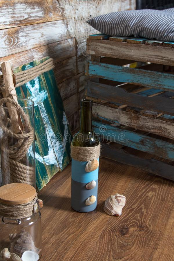 Bottle with shells, anchor painting, sea theme on wooden background.  stock image