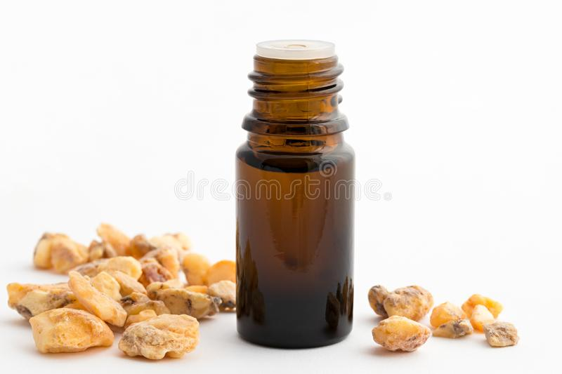 A bottle of styrax benzoin essential oil with benzoin resin. A bottle of styrax benzoin essential oil with styrax benzoin resin on a white background royalty free stock photography