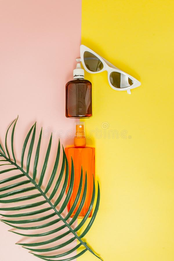 Bottle sunblock on bright square yellow and pink background. The concept of the resort at sea, summer time. Top view, flat lay,. Minimalism, copy space stock photo