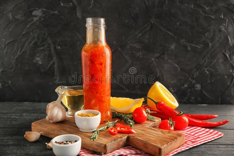 Bottle with tasty sauce, vegetables and condiments on table stock photography