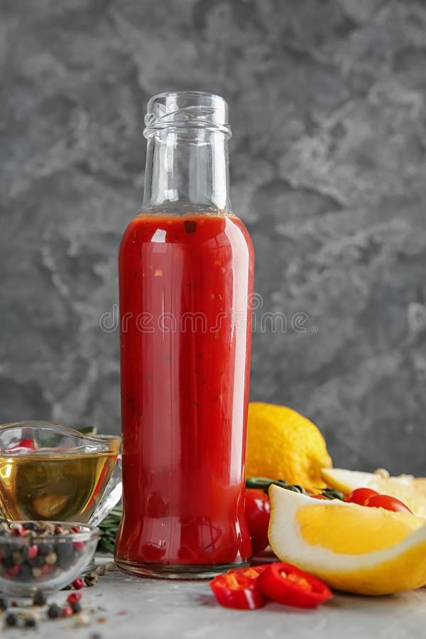 Bottle with tasty tomato sauce, vegetables and condiments on table stock images