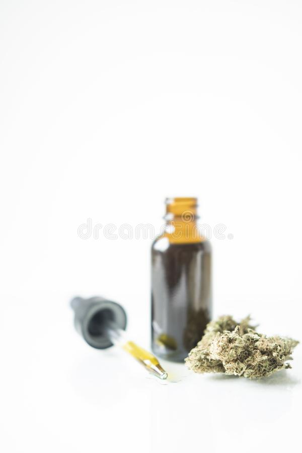 Tincture bottle with cannabis bud and dropper royalty free stock photo