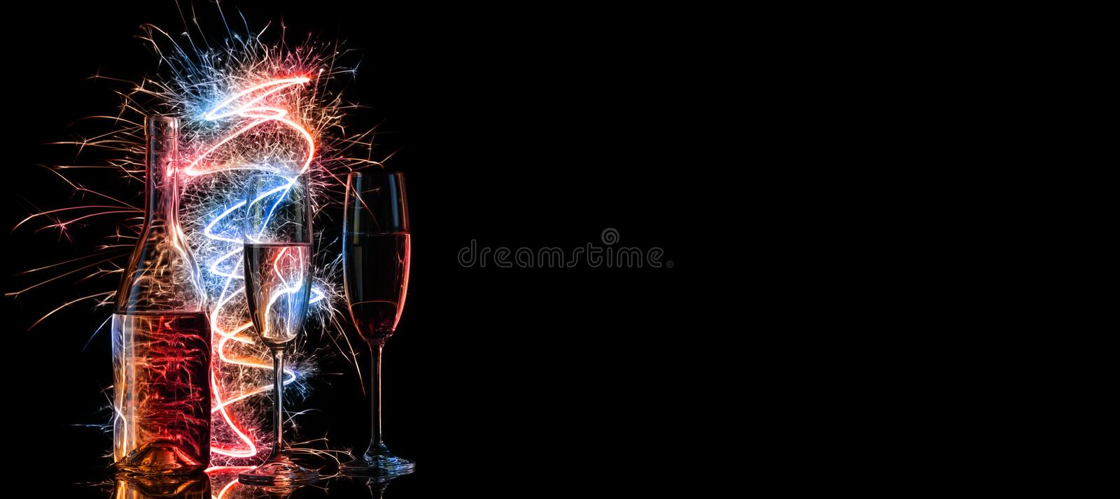 Bottle and two glasses of champagne in multi-colored sparklers on black background royalty free stock images