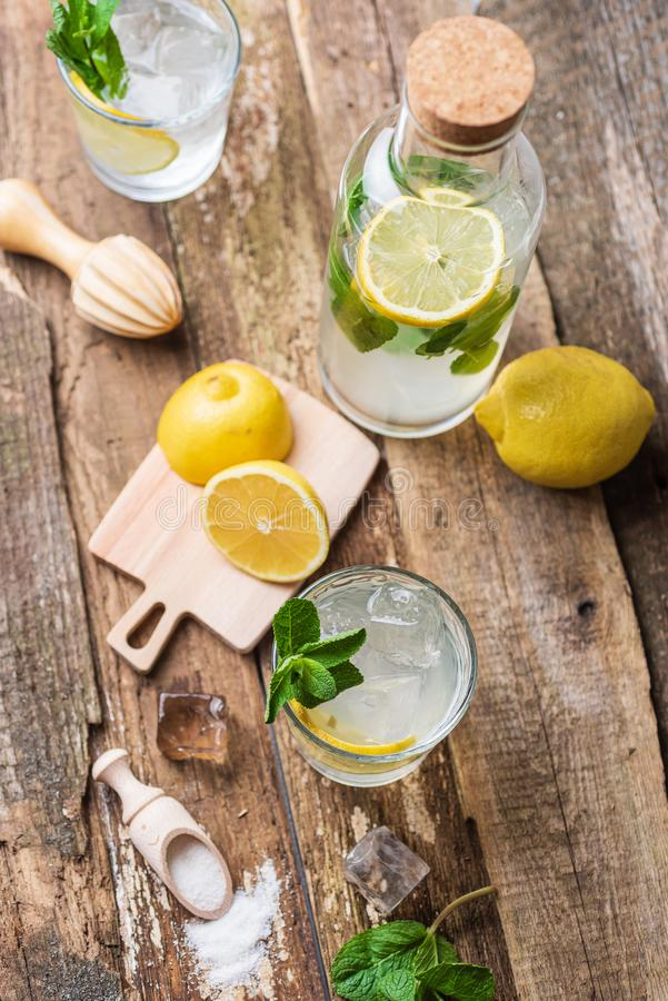 Bottle and two glasses of fresh lemonade with lemon slices, mint and ice on old wooden planks stock image