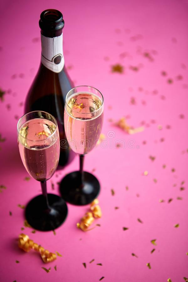 Bottle and two glasses full of sparkling champagne wine with golden decoration royalty free stock images