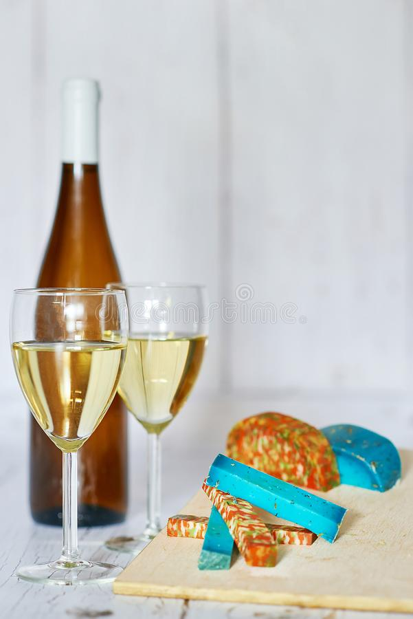 Bottle and two glasses of white wine, white grape and variation of ucommon cheeses on a wooden background stock photo
