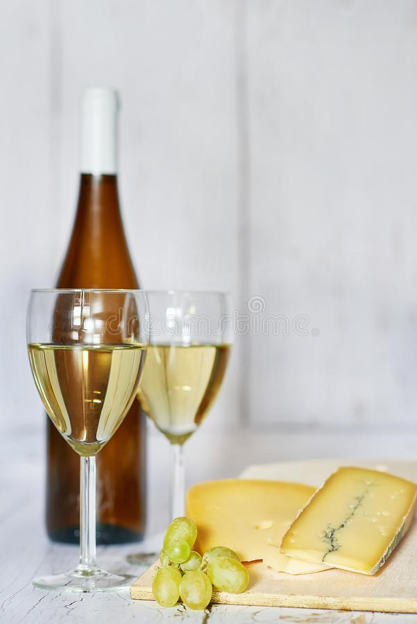 Bottle and two glasses of white wine, white grape and blue cheese on a wooden background royalty free stock images